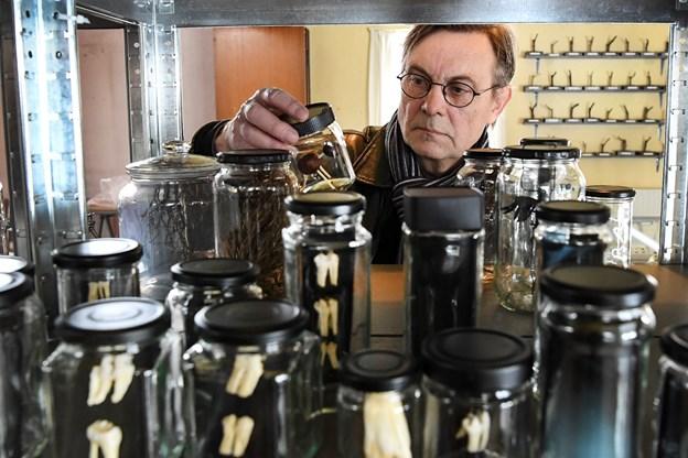 Bruno Kjær ved nogle af de mange glas fra udstillingen indeholdende forskellige genstande.