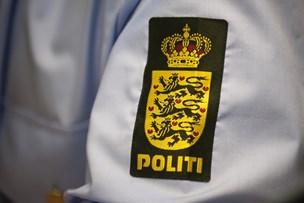 Fuld betjent på bar med politiskilt om halsen