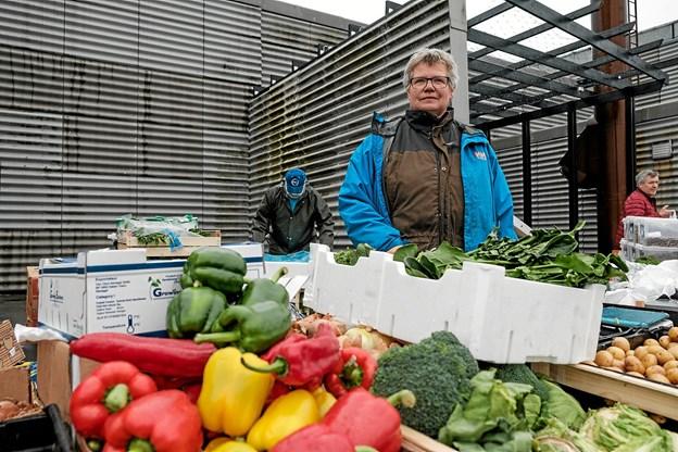 Bente - og i baggrunden Trevor lod sig ikke gå på af regn og blæst. De har fået en god plads udendørs til deres grøntsager. Ostemanden fra Vindblæs havde også valgt en placering ude. Foto: Lasse Sand