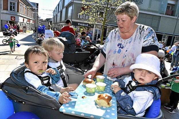 Mette Abildgaard havde lavet et praktisk bord midt i barnevognen. det passe Wilson, Jens og Christian godt. For så kunne de sidde og spise masser af is. Foto: Ole Iversen