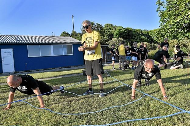 Team Hortensia: Michael Overgaard (tv), Klaus Østergaard og Bent Steensgaard kæmper med det. Manden i rebet må ikke røre rebene - det udløser 3 x armbøjninger. Foto: Ole Iversen