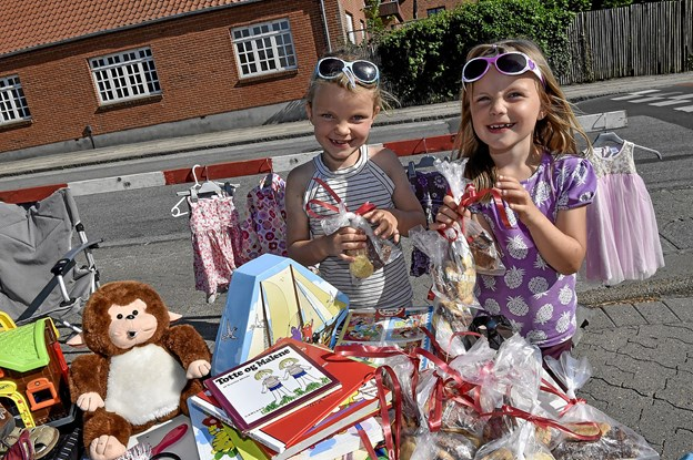 Tvillingerne Line og Trine Bendtsen havde tømt deres værelse for udgået legetøj og forsøgte at omsætte det til friske kroner. Det havde også kager som de solgte. Foto: Ole Iversen