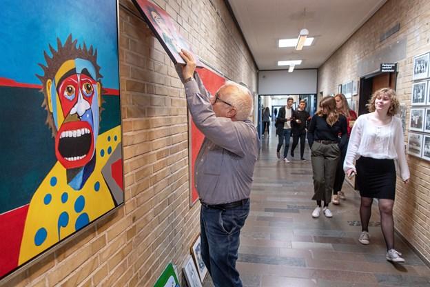 Henrik Damsgaard har brugt de sidste dage på at hænge de 28 værker op på en af gymnasiets mest befærdede gange. Udstillingen rummer både tegninger og malerier med akvarel og akrylmaling.