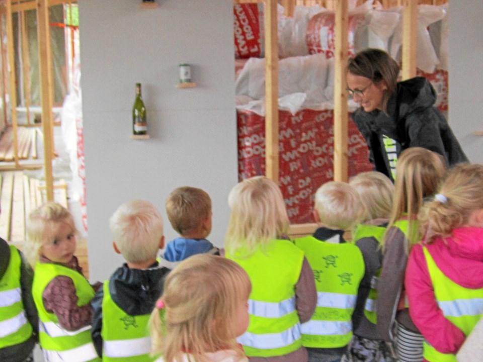 Daglig leder af Svinget Helle Birch Christensen instruerer børnene i hvordan de med små sten hver især skal ramme flasker og dåser placeret på væggen for på den måde at få forståelse for materialernes forgængelighed, som er hovedprincippet i bæredygtigt byggeri.