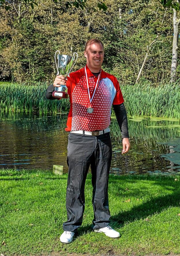 En glad vinder med pokalen og det danske mesterskab i golf for døve. Foto: Mogens Lynge