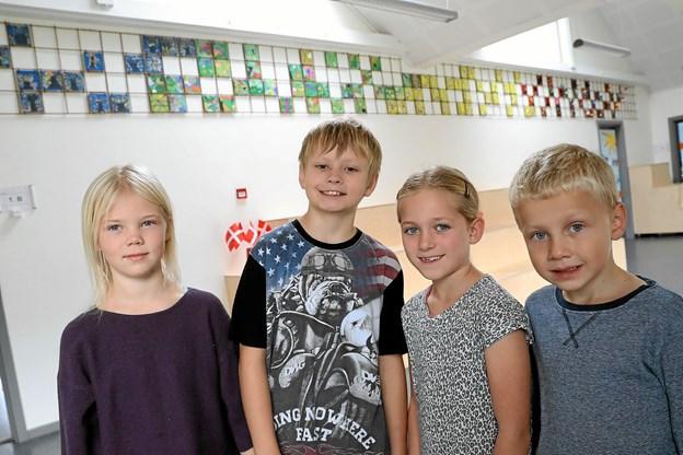 Elever fra 0. til 3. årgang har kreeret det store kunstværk. På billedet er det fra venstre Liva fra 1. klasse, Asger fra 3., Freya fra 2. og Jacob fra 0. klasse foran værket. Foto: Allan Mortensen