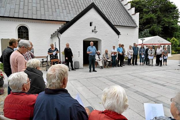 Formanden for menighedsrådet Ole-Jan Staun-Pedersen fortæller om det lange tilløb med at få de to hovedstier asfalteret og området foran kirken belagt med fliser.? Foto: Niels Helver