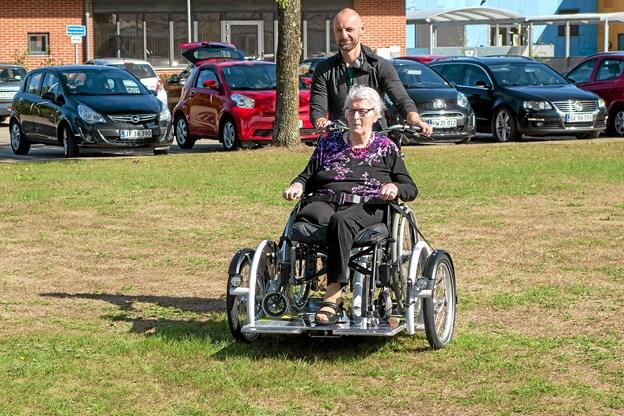 Klaus Frederiksen fra cykelleverandøren tager Birthe Jensen med ud på den allerførste tur på den nye kørestolscykel. Foto: Niels Helver