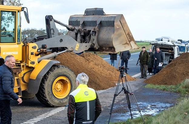 Landmand lukker vej i protest: Dumper jord og bigballer på vejen