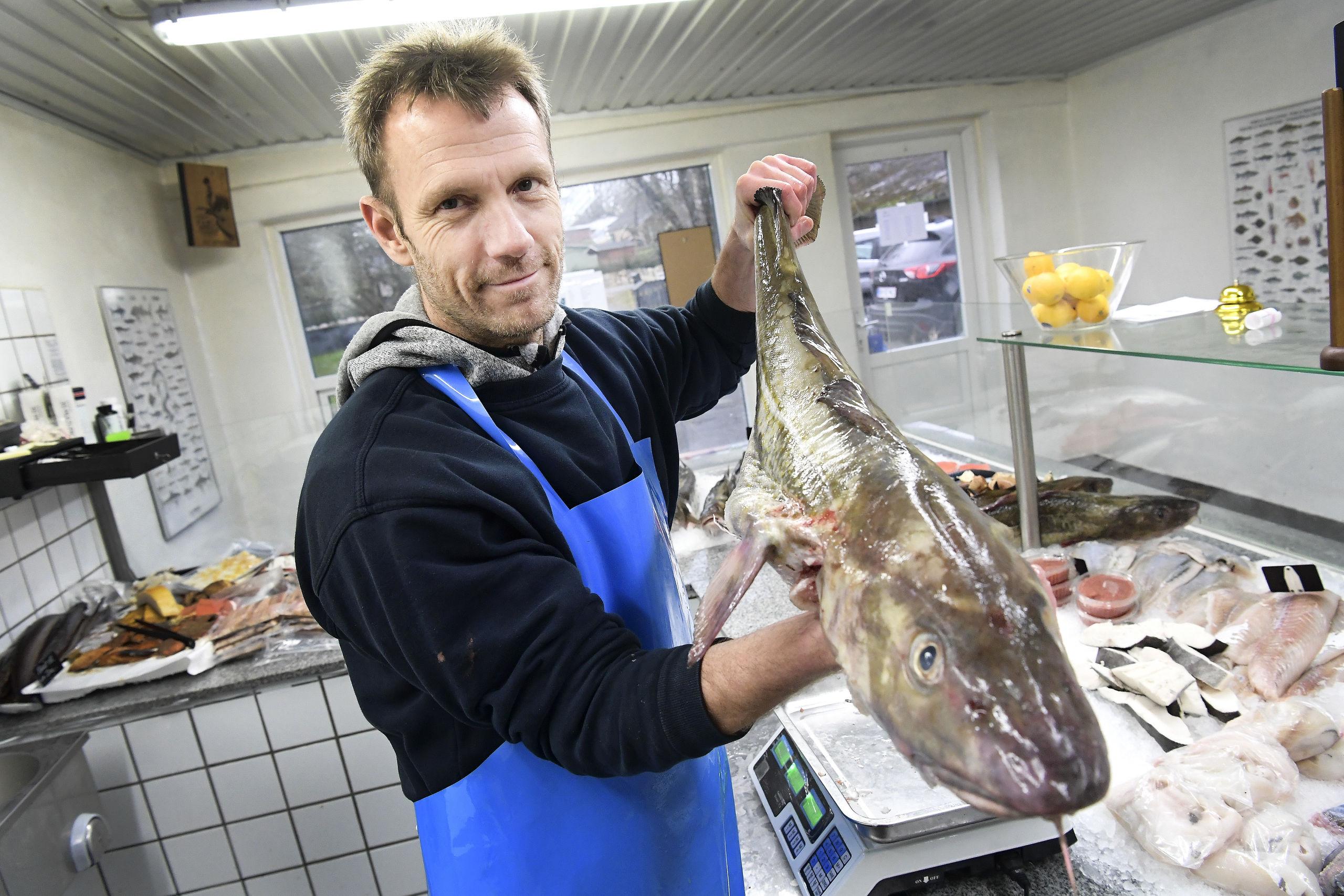 Værsgo - og nyd endelig synet. Fiskehandler Johnny Melchior Nielsen viser her et pragteksemplar af en torsk på ikke mindre end 5,8 kilo. Foto: Michael Koch