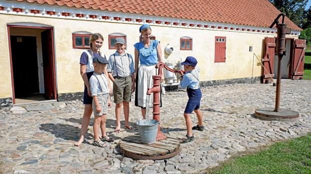 Husmandsfamilien, Asle, Freja, Valdemar og Tinna, ved brønden, hvor Magne pumper vand. Foto: Niels Helver Niels Helver