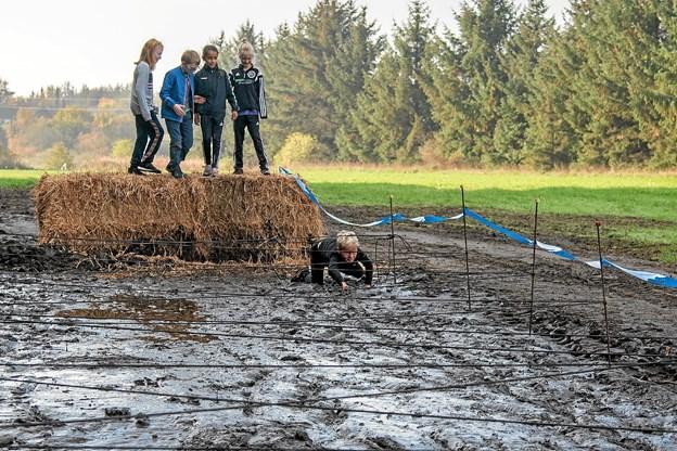 William er først ude i forhindringen med mudder. Magnus, Nadja, Nellie og Isabella tøver et øjeblik, inden de også kaster sig ud i mudderbadet. Foto: Niels Helver