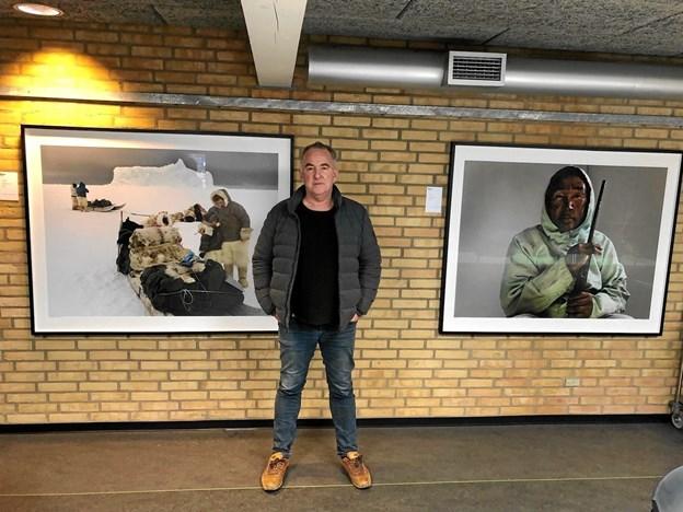 Henrik Saxgren foran to af sine billeder, som hænger på Vesthimmerlands Gymnasium og HF i Aars. Privatfoto