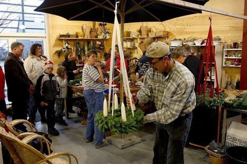 Der er mange kunder i butikken - nogle mangler stadig at få købt en adventskrans. Her er det medarbejder Villy Kruse, der monterer de sidste lys på kransen.
