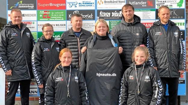 I midten står Kate H. Mathiasen, PR for FIF fodbold, sammen med Claus Nielsen (tv) fra H.J. Nielsen Automobiler i Fjerritslev og Lars Lyebalk (th) fra XL-byg Tømmergaarden, Fjerritslev, samt en del af klubbens trænere og assistenttrænere, som er iført de flotte jakker. Privatfoto