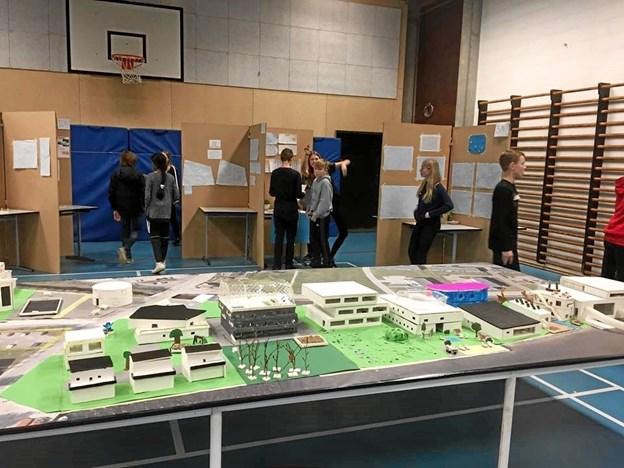 Et udsnit af elevernes projekter sat op på dug med satellitbillede over området omkring Hobro Havn. I baggrunden ses nogle elever og nogle af gruppernes stande. Privatfoto