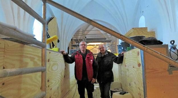Jens Juhl og Jørgen Schierup på kirkegangen mellem de midlertidigt neddækkede kirkebænke. Foto: Kirsten Olsen