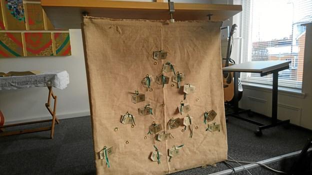I kirkesalen i Aagade hænger et lærred med små papkasser på, så menigheden har kunnet følge med i, hvor mange julehjælpskasser, man løbende er nået op på at kunne uddele i år.