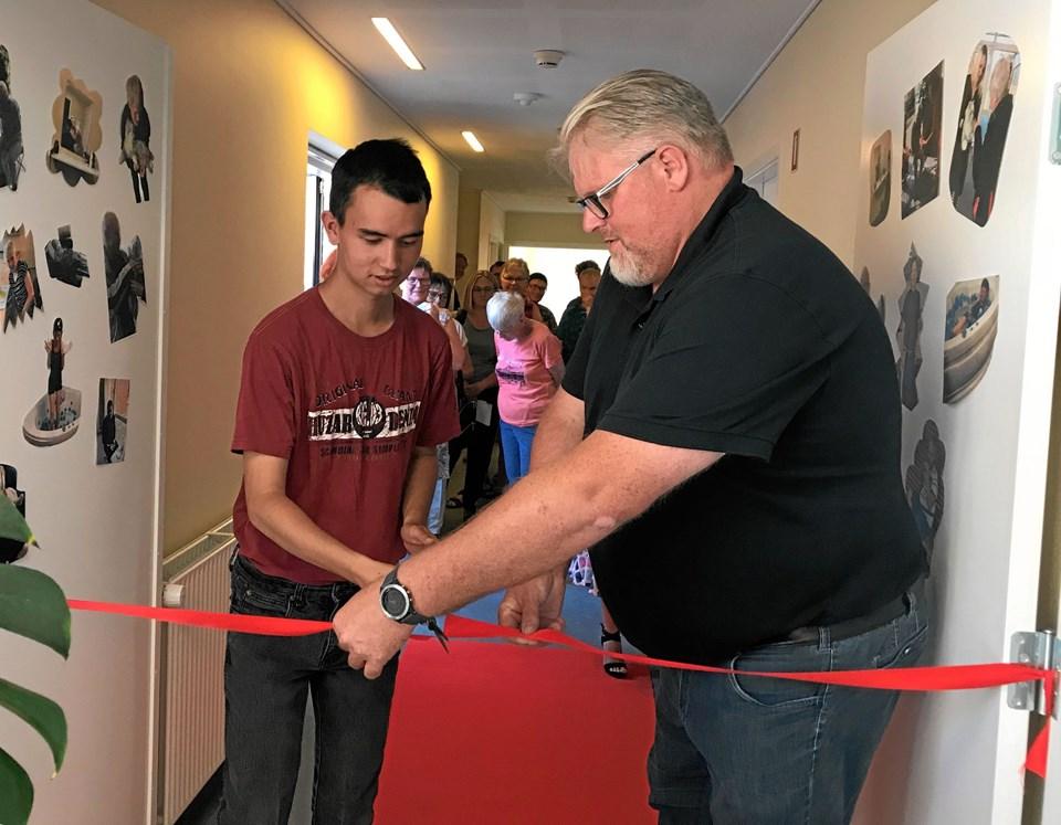 Beboer Christian Madsen og udvalgsformand Jan Andersen får ved fælles hjælp klippet den røde snor til wellnessafdelingen over.