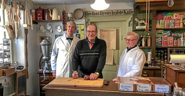 På billedet ses Hans Jørgen Hartmann i færd med at skære Hartmann-spegepølsen til, flankeret af købmand Jens Christensen til venstre, og købmand Poul Erik Christensen til højre.