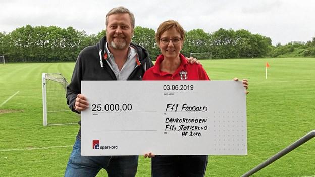 Jette Bruun Christensen overrækker her 25.000 kroner til Anders Brandt fra FfI Fodbold