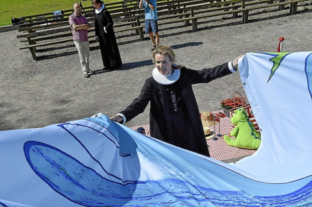 Duen er friluftsgudstjenestens symbol. Her tjekker Anne Marie Nande Kraft det store banner, som skal hænges op på scenen i Christiansgave. Foto: Ole Iversen