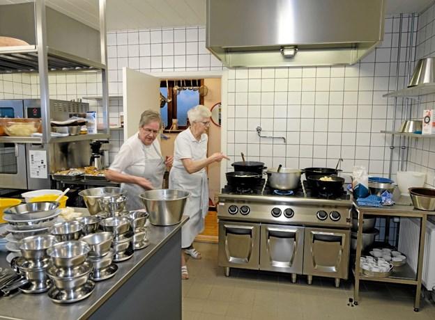 Huset formand Bodil Pedersen og Karen Sørensen har travlt i køkkenet, for snart skal der serveres flæskesteg med alt det traditionelle tilbehør til 105 gæster. Foto: Niels Helver Niels Helver