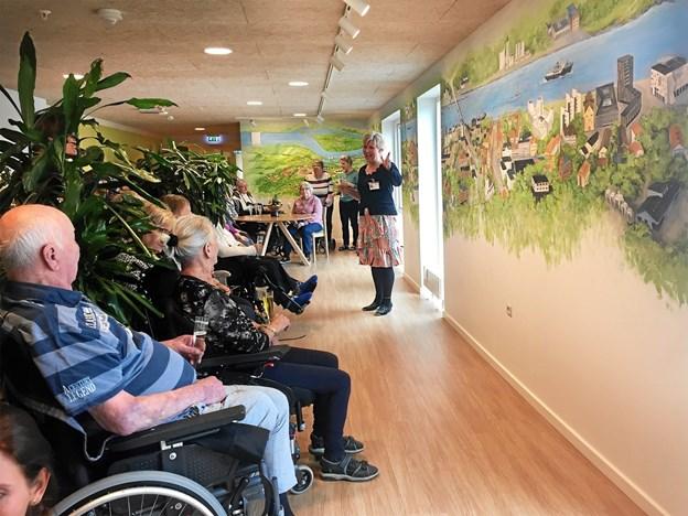 Plejehjemsleder Marianne Savkov holder indvielsestale for de mange beboere, pårørende og personale, der var mødt frem, for at se det store vægmaleri af Aalborg by.