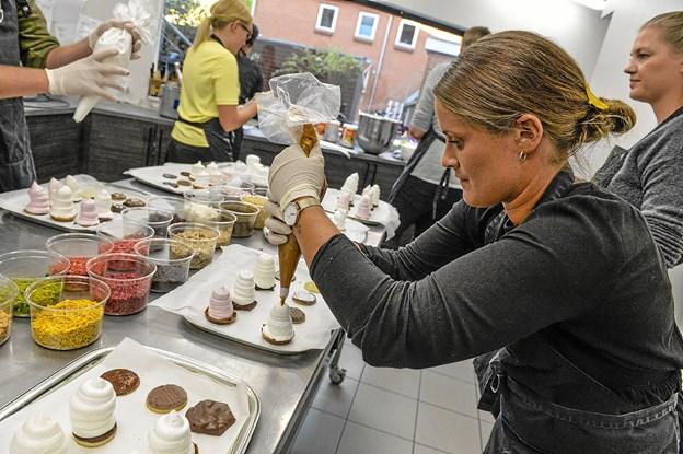 Dyb koncentration hos Pernille Justesen, der er i gang med at fylde flydende karamel inde i flødebollen, og det må ikke bule ud gennem siden.Foto: Ole Iversen