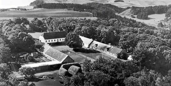 Bramslevgaard fotograferet i 1954. De oprindeligt 700 tønder land jord blev ved udstykning og salg i 1920 reduceret til de nuværende 127 tønder land. Heraf 50 tønder land med bakker og skov, der vender ned mod Mariager Fjord.? Selve Bramslev Bakker, hvorpå der vokser nogle af Danmarks største enebærbuske, blev i 1933 fredet. Historisk foto