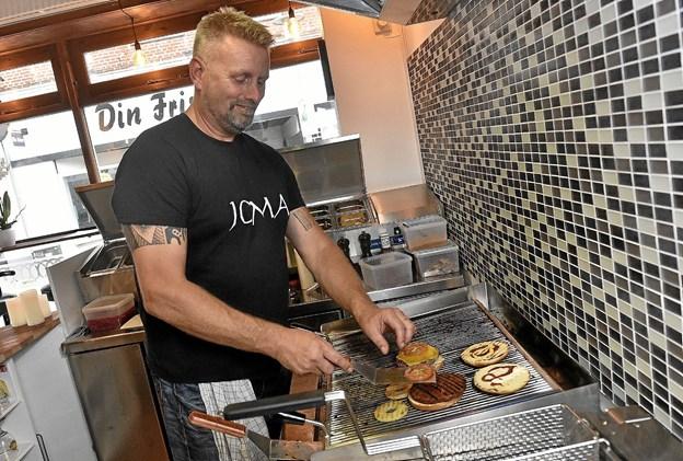 """Joe Uldahl har selv """"opfundet"""" sine foreløbigt syv burgere, hvor han laver en del af fyldet, som altid er blødt, på grillen mens bøffen steger. Det er blandt andet stegte tomatskiver med krydderi og stegt ananas, som indgår i en af burgerne. Foto: Ole Iversen"""