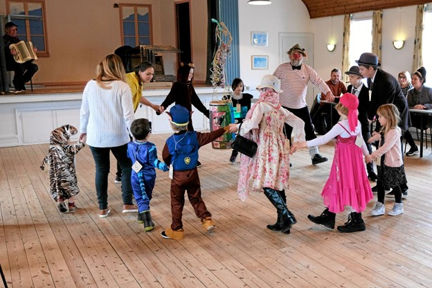 """Peter Jacobi og de udklædte børn går syngende rundt om fastelavnstønden, inden festen med at slå """"Katten af tønden"""" begynder. Jørgen Olsen er på scenen og spiller til sanglegene. Foto: Niels Helver"""