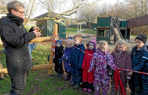 Daglig leder af Børnehuset Helle Mørkbak Højrup fortæller børnene om traditionen med at klippe den røde snor, når noget nyt skal tages i brug for første gang. Foto: Niels Helver Niels Helver