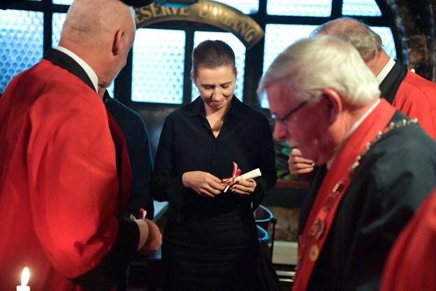 Mette Frederiksen fik i forbindelse med optagelsen overrakt både jubilæumsbog og lavs-nål, som hun her studerer med den største interesse.
