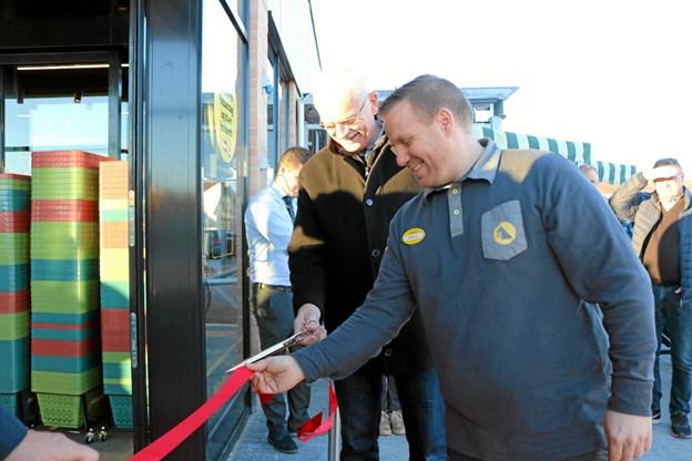 Butikschef Rasmus Bak og 1. Viceborgmester Bjarne Kvist klippede med fælles hjælp den røde snor der markerede åbningen af Netto i Sæby. Foto: Tommy Thomsen