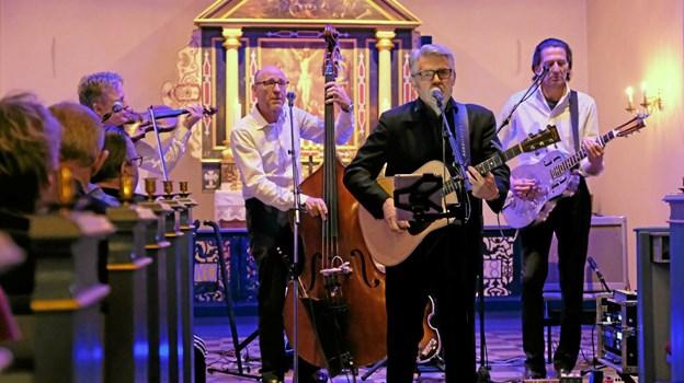 Karsten Holm og Cash Trioen var i Lendum Kirke, hvor de i sangen beskrev Johnny Cash. Karsten Holm er forsanger. Knud Erik Steengaard spiller violin. Bjørn Petersen kontrabas og Martin Blom spiller på akustisk guitar og resonator. Foto: Niels Helver
