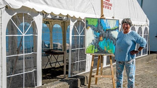 Kunstneren Birthe Kjærsgaard, ses her med et af sine malerier foran teltet, som sommeren igennem er til kursus, for dem som gerne vil lære malekunsten. Foto: Mogens Lynge