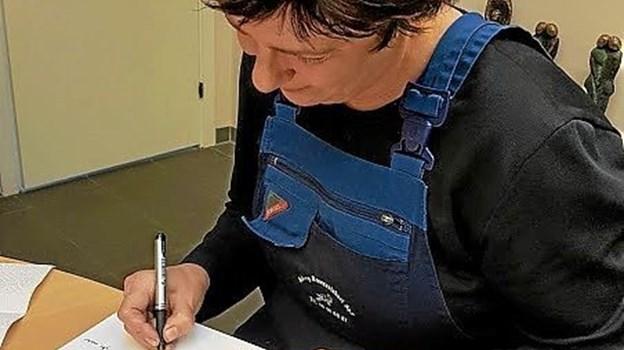 Bog nummer 73 signeres som alle andre med personlige kommentarer. Foto: Karl Erik Hansen Karl Erik Hansen