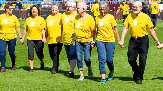 Det er kun fightere, der må have disse gule T-shirt på som symbol på, at de har eller har haft kræft. Her ses gruppen, som gik ind på banen sammen Hobro IK-spillerne i sidste hjemmekamp mod Vejle. Privatfoto
