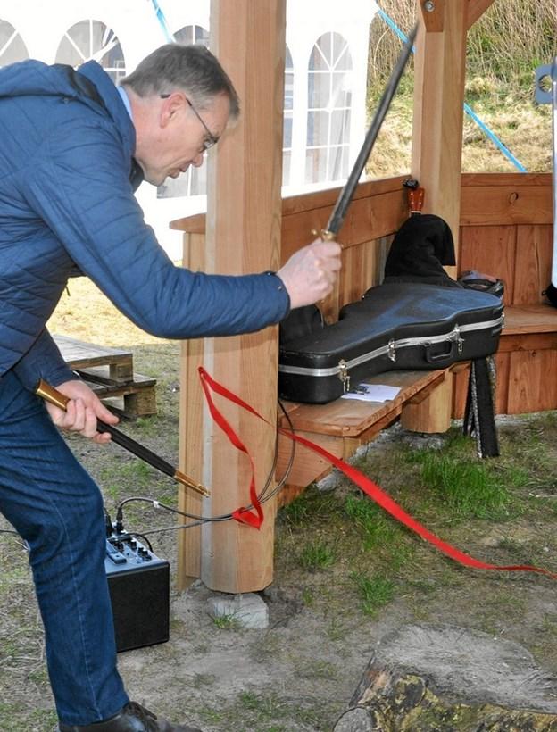 Den klassiske overklipning med saks af et rødt bånd var af historiske grunde erstattet af hug med et sværd. Borgmester Mikael Klitgaard måtte bruge adskillige hug, før det lykkedes. Foto: Ole Torp Ole Torp