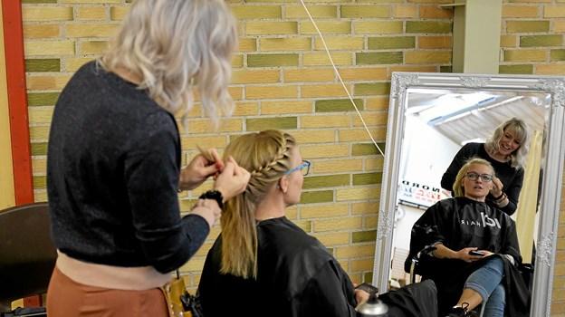 Louise Akselsen fra Frisør Gården sætter hår på Julie Leerskov, initiativtageren til kunstmessen og medlem af Skolekredsudvalget. Foto: Niels Helver