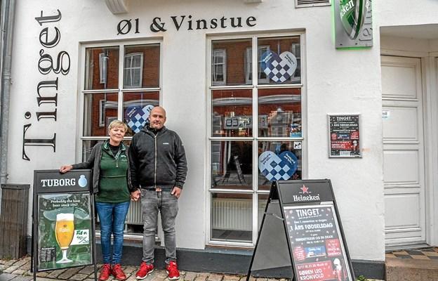 """Værtsparret Malene Jacobsen og Allan Sørensen foran """"Tinget"""" på 1. års dagen. Parret har mange arrangementer og bl. a. musik fredag aften, når sneen falder. Foto: Mogens Lynge"""