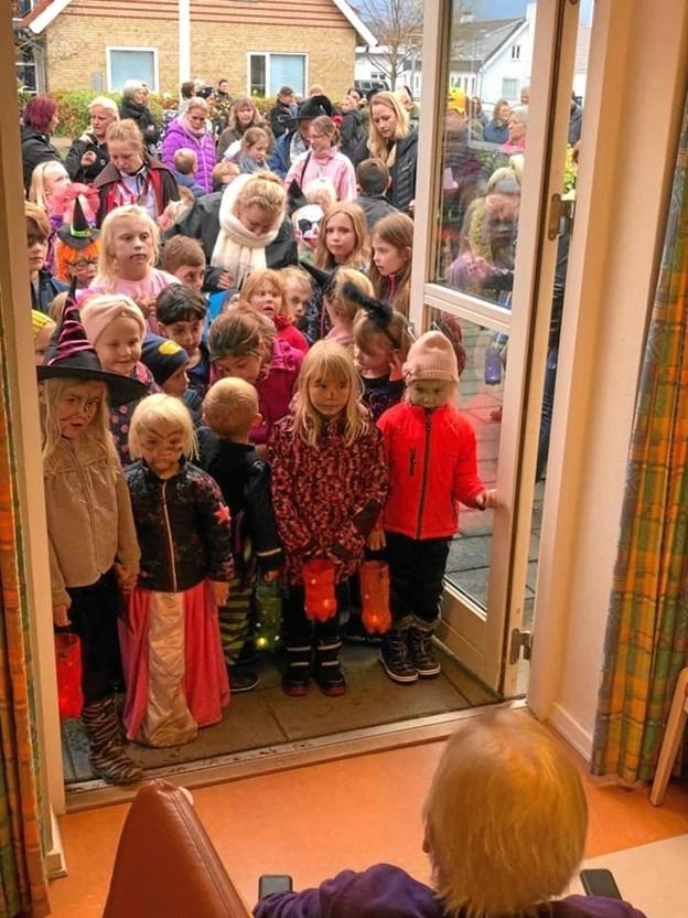 Børn og forældre i Gedsted synger Halloween-sange for de ældre på Søndervang. Privatfoto