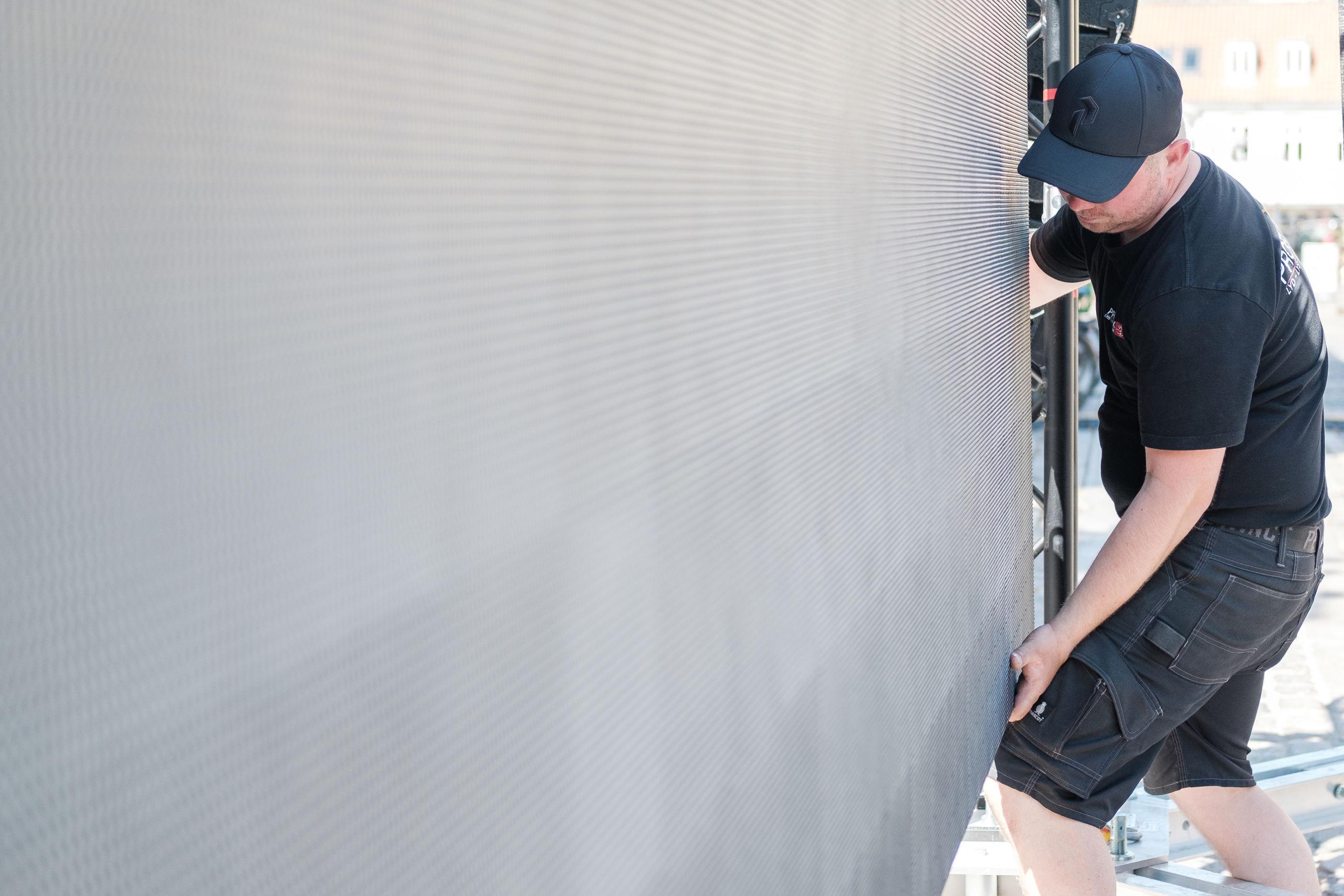 På Gammeltorv arbejdes på højtryk for at blive klar til VM på storskærm. Det er Mads Lange, der samler storskærmen. Foto: Lasse Sand