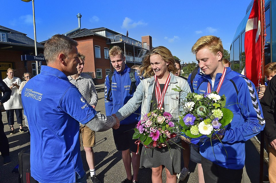 Jesper Hovmark ønsker de to medaljevindere tillykke. I baggrunden svømmeklubbens fane. Foto: Ole Iversen