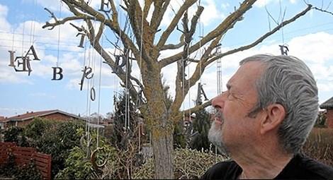 Forfatteren Tom Oxager med sit bogstavtræ, der skabte stor inspiration. I hvert fald indtil en ordblind storm væltede træet ...