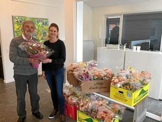Præsident i Lions Hobro, Knud Trier, overrækker blomsterbuketterne til Charlotte Thejl Nielsen fra Hobro Efterskole.     Privatfoto
