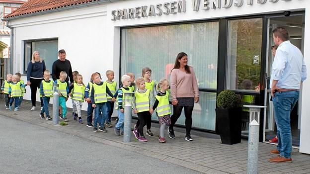 """Afdelingsdirektør Mads Nielsen og kasserer Helle Kongshøj byder """"De gule veste"""" velkommen. De mange børn er kommet for at sige tak for donationen af sikkerhedsvestene. Foto: Niels Helver"""