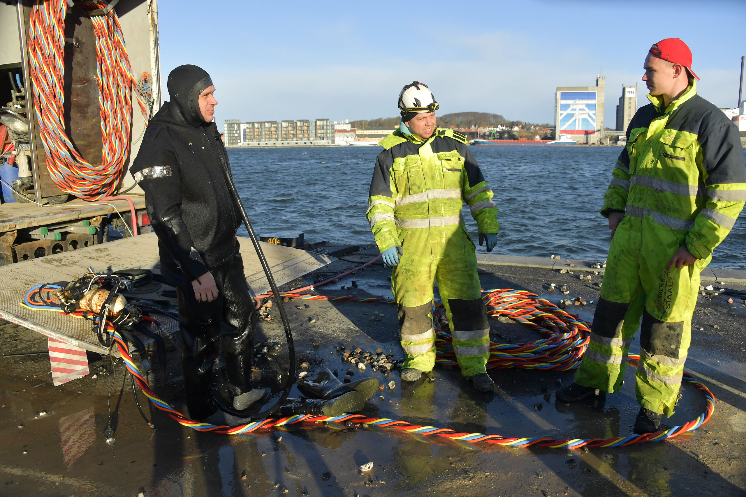 Der er briefing på kajkanten, og dykkerne Sonny Rasmussen (tv) og Michael Nielsen i midten lytter til meldingen fra lineholder Jon G. Andersen. Foto: Claus Søndberg
