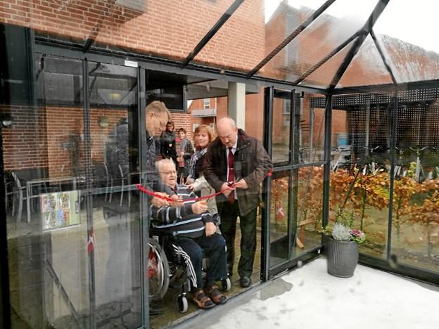 Borgmester Mikael Klitgaard (V), beboer Viggo Egon Anton Jensen og Karsten Frederiksen (K) fik æren af at klippe den røde snor til det nye orangeri.
